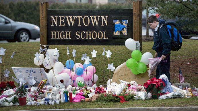 A student looks for a place to leave flowers at a makeshift memorial for the victims of the Sandy Hook Elementary School shooting at the entrance of Newtown High School December 18, 2012 in Newtown, Connecticut. (AFP Photo / Brendan Smialowski)