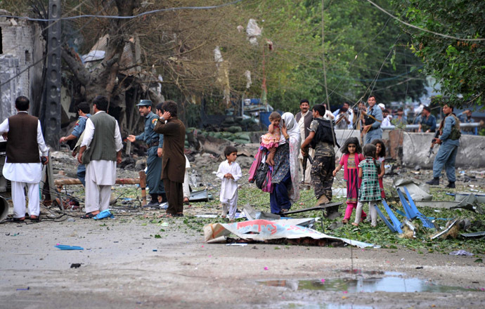 Afghanistan policemen and civilians walk at the siTe of a suicide attack in front of the Indian consulate in Jalalabad on August 3, 2013. (AFP Photo/Noorullah Shirzada)