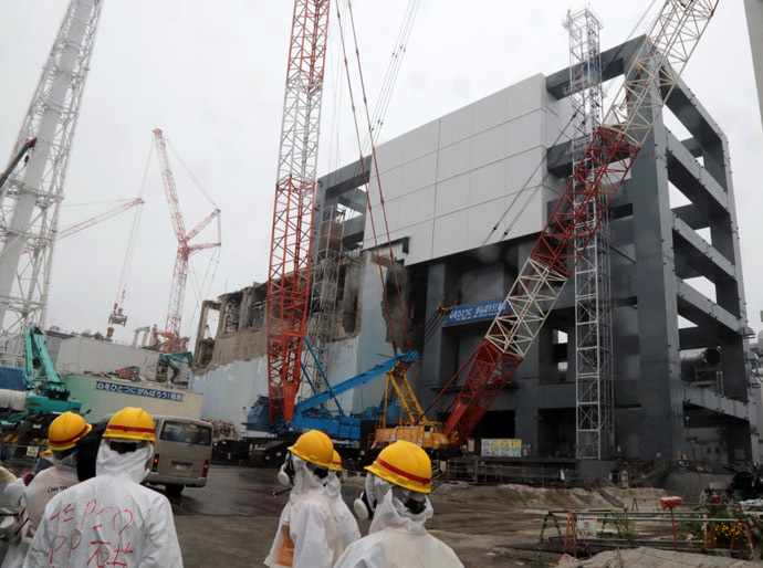 Reporters and Tokyo Electric Power Co workers look up the unit 4 reactor building during a media tour at TEPCO's Fukushima Dai-ichi nuclear plant in the town of Okuma, Fukushima prefecture in Japan on June 12, 2013. (AFP Photo)