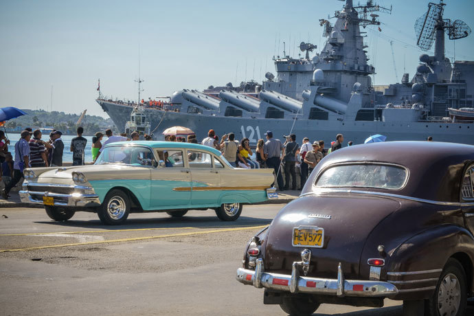 "Vintage US-made cars pass by as Cubans watcht the ""Moskva"" Russian guide missile cruiser arriving at Havana's harbour, on August 3, 2013.(AFP Photo / Adalberto Roque)"