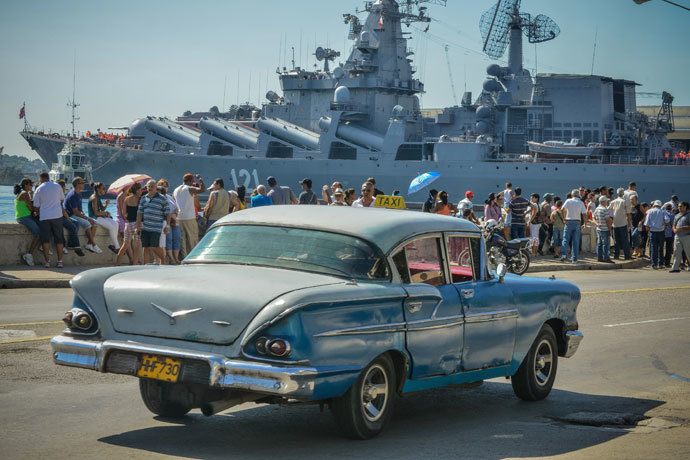 "A vintage US-made car passes by as Cubans wave at the ""Moskva"" Russian guide missile cruiser arriving at Havana's harbour, on August 3, 2013.(AFP Photo / Adalberto Roque)"