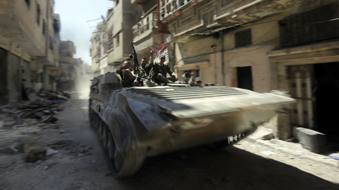 Soldiers of the Syrian government forces patrol on a tank in a devastated street on July 31, 2013 in the district of al-Khalidiyah in the central Syrian city of Homs. (AFP Photo / Joseph Eid)