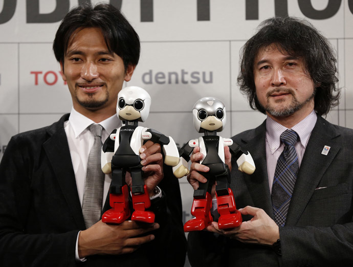Tomotaka Takahashi (L), CEO of Robo Garage Co and project associate professor, research centre for advanced science and technology, the University of Tokyo, and Fuminori Kataoka, project general manager in the Product Planning Group of Toyota Motor Corp, hold humanoid communication robots Kirobo and Mirata respectively during their unveiling in Tokyo June 26, 2013. (Reuters/Toru Hanai)