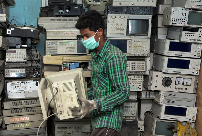 An Indian worker carries a defunct CRT Monitor for disassembly at Ash Recyclers, a government approved e-waste management firm in Bangalore (AFP Photo / Manjunath Kiran)