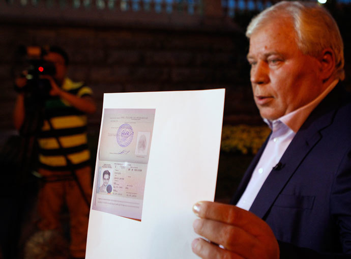 Lawyer Anatoly Kucherena shows a picture of fugitive former US spy agency contractor Edward Snowden in his new refugee documents granted by Russia during a news conference in Moscow August 1, 2013. (Reuters / Maxim Shemetov)
