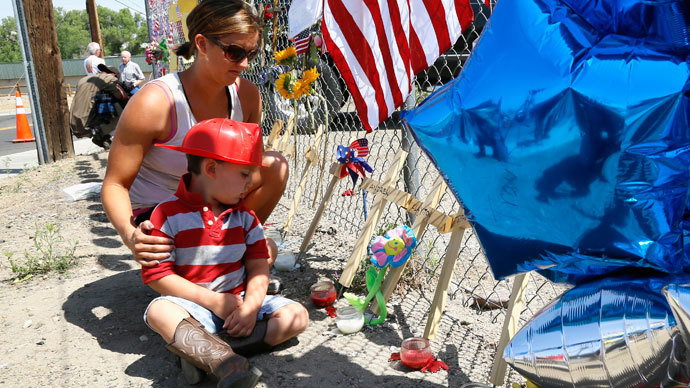 Casen Beyea, 3, wearing a toy fireman helmet looks at the cross for Andrew Ashcrast with his mother Christine at a memorial for the 19 firefighters killed in the nearby wildfire, in Prescott, Arizona July 2, 2013.(Reuters / Rick Wilking)