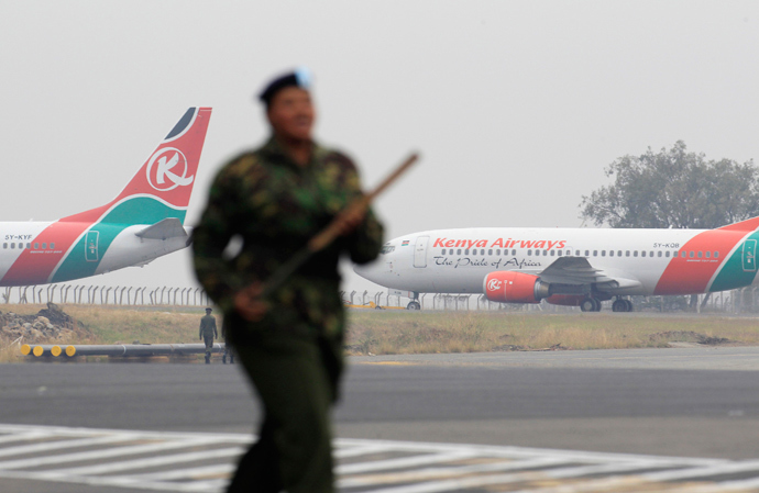 Kenya Airways aircrafts stay grounded after a huge fire left all flights suspended at the Jomo Kenyatta International Airport, as a soldier patrols the grounds, in Kenya's capital Nairobi August 7, 2013 (Reuters / Noor Khamis)