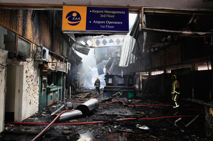 Fire fighters walk amid debris from a fire at the Jomo Kenyatta International Airport in Kenya's capital Nairobi August 7, 2013 (Reuters / Noor Khamis)