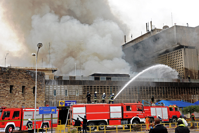Fire crews work to put out a fire outside the burning Jomo Kenyatta international airport on August 7, 2013 (AFP Photo / Stringer)