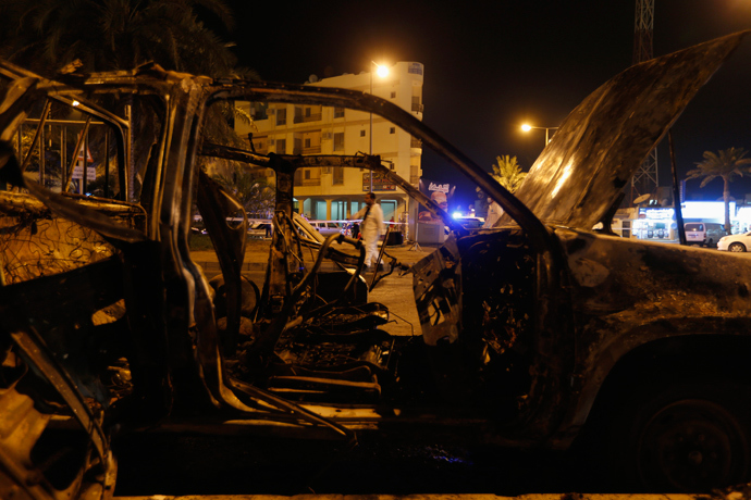 A bomb specialist (C) looks for evidence in front of an exploded vehicle in Budaiya, west of Manama August 3, 2013 (Reuters / Hamad I Mohammed)
