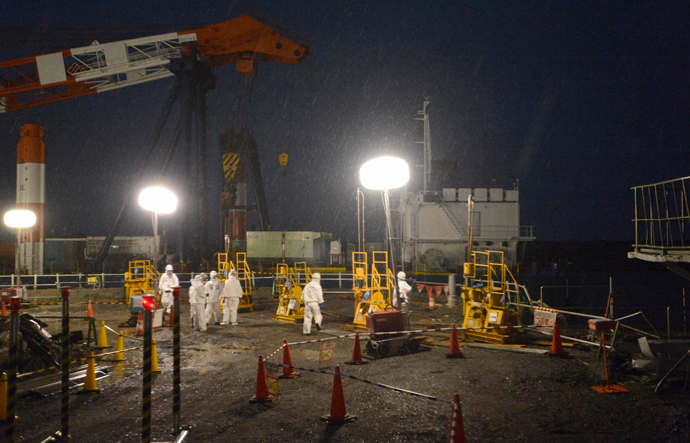 Workers wearing protective suits and masks operate a soil improvement work site of the shore barrier to stop radioactive water from leaking into the sea, near the No.1 and No.2 reactor buildings of the tsunami-crippled Fukushima Daiichi nuclear power plant (Reuters / Kyodo)