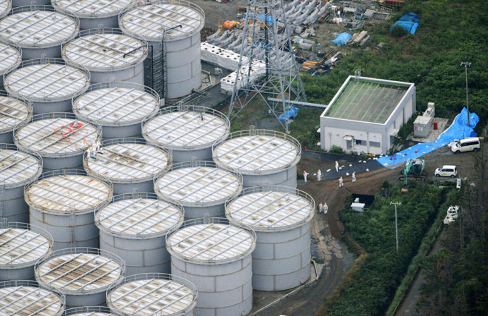 An aerial view shows workers wearing protective suits and masks working atop contaminated water storage tanks at Tokyo Electric Power Co. (TEPCO)'s tsunami-crippled Fukushima Daiichi nuclear power plant in Fukushima, in this photo taken by Kyodo August 20, 2013. (Reuters/Kyodo)