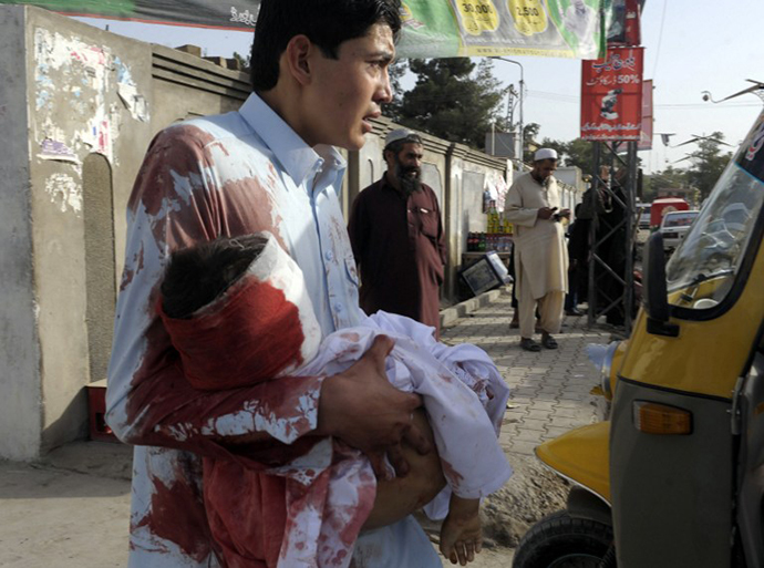 A Pakistani mourner carries the body of a child outside a hospital in Quetta on August 9, 2013, following an attack by gunmen on a mosque. (AFP Photo / Banaras Khan)