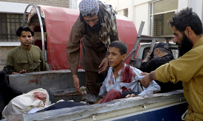 Pakistani bystanders help an injured Muslim youth as he sits in a pickup truck amidst bodies outside a hospital in Quetta on August 9, 2013, following an attack by gunmen on a mosque. (AFP Photo / Banaras Khan)