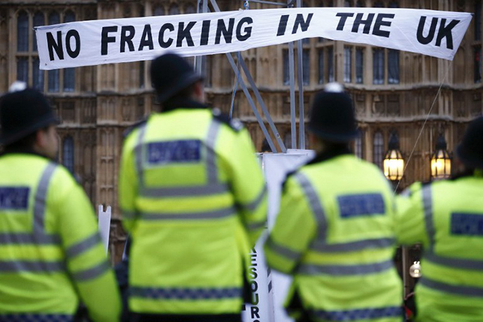 "British police secure the area where demonstrators erected a mock fracking rig with a banner reading ""No fracking in the UK"" in a protest against hydraulic fracturing for shale gas outside the Houses of Parliament in London (AFP Photo / Justin Sullivan)"