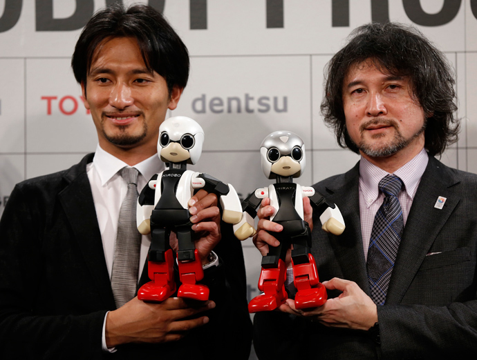 Tomotaka Takahashi (L), CEO of Robo Garage Co and project associate professor, research centre for advanced science and technology, the University of Tokyo, and Fuminori Kataoka, project general manager in the Product Planning Group of Toyota Motor Corp, hold humanoid communication robots Kirobo and Mirata respectively during their unveiling in Tokyo (Reuters)