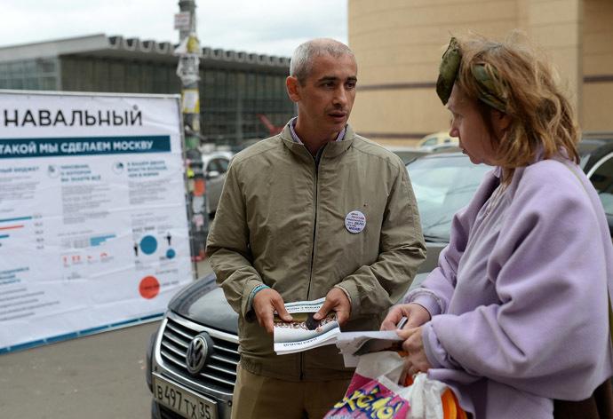 A member of Alexei Navalny's election campaign team provides information on Navalny's electoral program to a woman on a street near the Kursky Train Station. (RIA Novosti/Vladimir Pesnya)