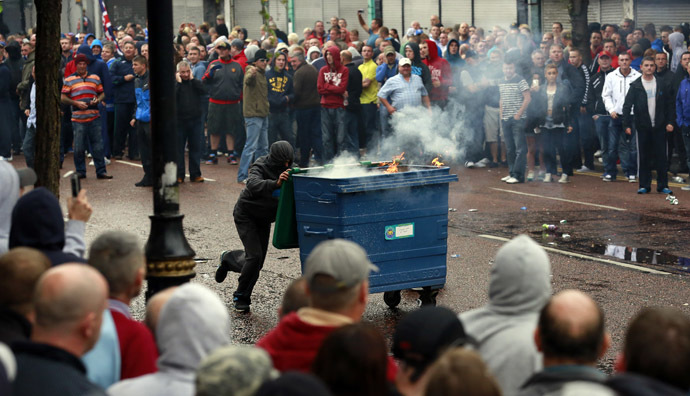 A loyalist protester pushes a garbage dumpster, that has been set alight, during clashes with the police as they wait for a republican parade to make its way through Belfast City Centre, August 9, 2013. (Reuters/Cathal McNaughton)