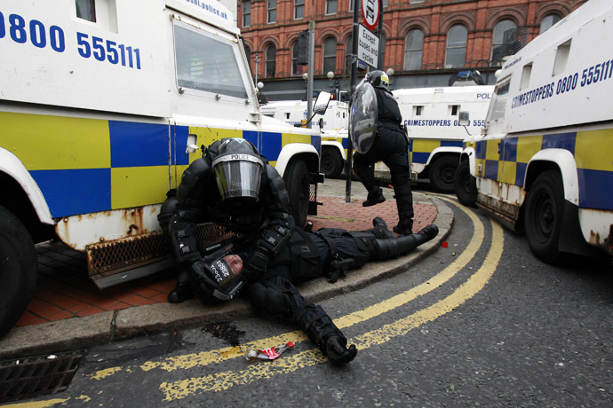 A police officer is tended to by a colleague after Loyalist protesters attacked the police with bricks and bottles as they waited for a republican parade to make its way through Belfast City Centre, August 9, 2013. (Reuters/Cathal McNaughton)