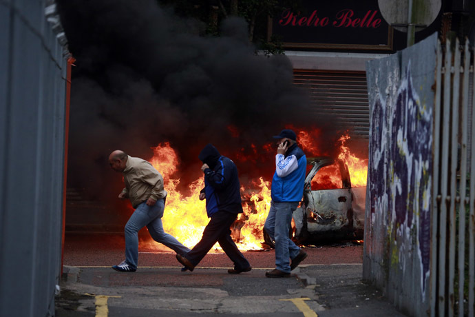 People run past a burning car after loyalist protesters attacked the police with bricks and bottles as they waited for a republican parade to make it's way through Belfast City Centre, August 9, 2013. (Reuters/Cathal McNaughton)
