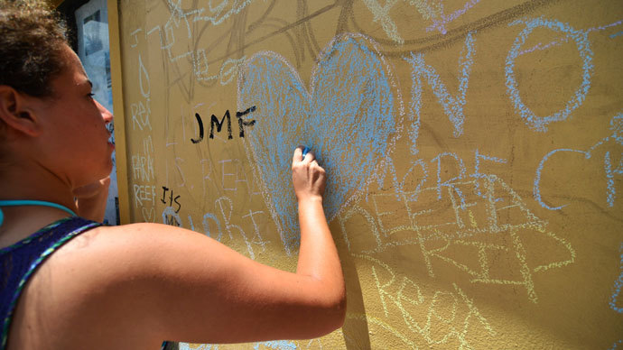 An attendee writes on a wall during a vigil for graffiti artist Israel Hernandez-Llach, who died after being shocked by a police officer's Taser, in Miami Beach, Florida August 10, 2013.(Reuters / Gaston De Cardenas)