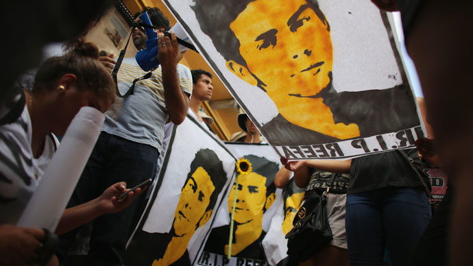 People hold posters during a vigil with a picture of 18-year-old graffiti artist Israel Hernandez-Llach, who died after being tasered by a Miami Beach police officer on August 10, 2013 in Miami Beach, Florida.(AFP Photo / Joe Raedle)