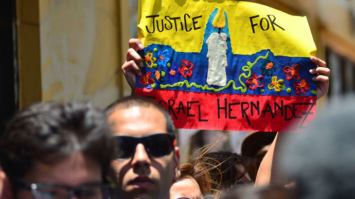 People hold up a poster during a vigil for graffiti artist Israel Hernandez-Llach, who died after being shocked by a police officer's Taser, in Miami Beach, Florida August 10, 2013.(Reuters / Gaston De Cardenas)