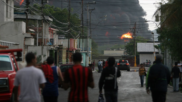 Local residents look towards the refinery of Guaraguao after a fire broke when a lightning struck a treatment pond, in Puerto la Cruz, state of Anzoategui, 220 km east of Caracas, on August 11, 2013.(AFP Photo / Jose Manuel Rondon)