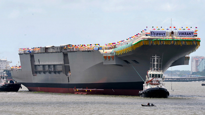 Tugboats guide the indigenously-built aircraft carrier INS Vikrant as it leaves the dock of the Cochin Shipyard after the launch ceremony in Kochi on August 12, 2013 (AFP Photo / Manjunath Kiran)