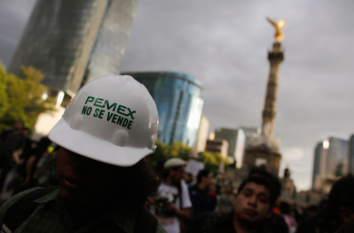 "A demonstrator wears a helmet with a sticker that reads ""Pemex is not for sale"" during a protest against the privatization of the state oil monopoly Pemex in Mexico City July 1, 2013.(Reuters / Tomas Bravo)"