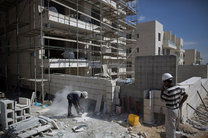 Laborers work at the construction site of a new housing project at the Jewish settlement of Gilo in Israeli annexed Arab east Jerusalem on August 12, 2013. (AFP Photo / Menahem Kahana)