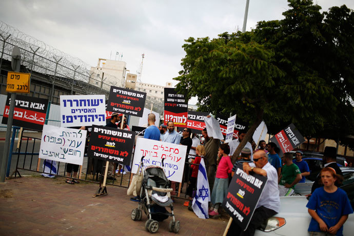 Protesters hold placards during a demonstration calling for the release of Israeli prisoners in response to Israel's expected release of Palestinian prisoners, outside the Ayalon prison in the city of Ramle near Tel Aviv August 13, 2013.(Reuters / Amir Cohen)