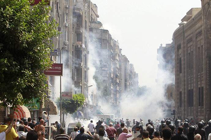 Supporters of ousted Egyptian President Mohamed Mursi run away from tear gas while local residents are seen in the foreground during clashes in central Cairo August 13, 2013. (Reuters / Mohamed Abd El Ghany)