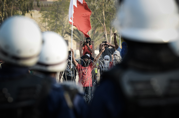 Riot police look on as Bahraini protestors shout anti-regime slogans and wave the national flag as they stand behind barbed wire placed by riot police during demonstration against the ruling regime in the village of Shakhora, west of Manama, on August 14, 2013 (AFP Photo / Mohammed Al-Shaikh)