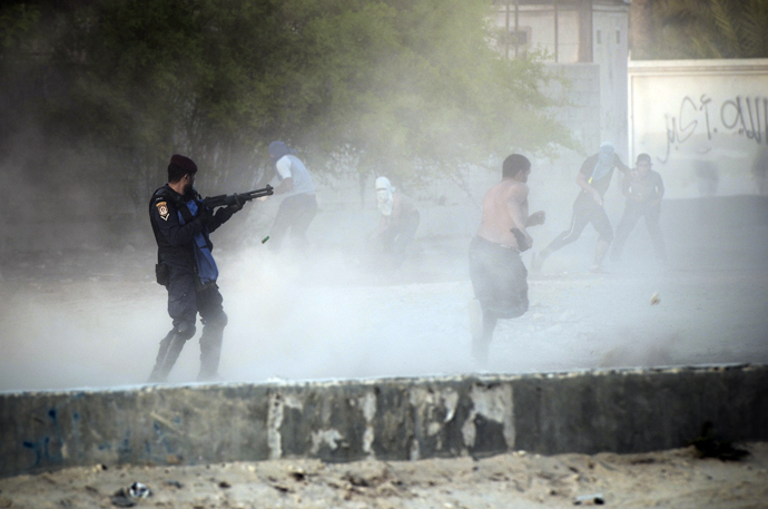 A Bahraini riot policeman ( L ) fires bird shot toward anti-government protestors during demonstration against the ruling regime in the village of Shakhora, west of Manama, on August 14, 2013 (AFP Photo / Mohammed Al-Shaikh)