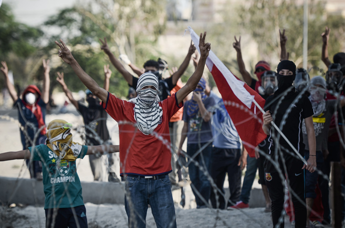 "Bahraini protestors flashing ""V"" sign for victory, stand behind barbed wire placed by riot police during demonstration against the ruling regime in the village of Shakhora, west of Manama, on August 14, 2013 (AFP Photo / Mohammed Al-Shaikh)"