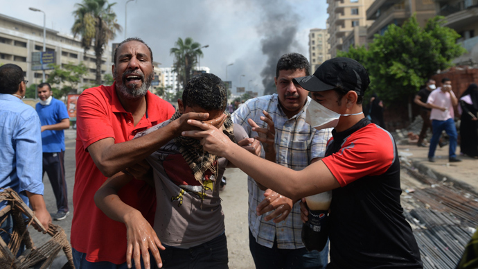 Supporters of Egypt's ousted president Mohamed Morsi and members of the Muslim Brotherhood run from tear gas smoke shot by police to disperse a pro-Morsi camp, on August 14, 2013 in Cairo (AFP Photo / Khaled Desouki)