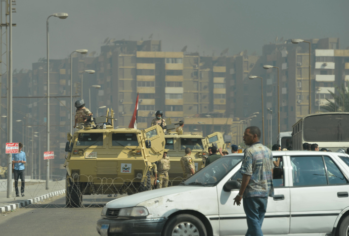 Egyptian military vehicles block a road leading to the Rabaa al-Adawiya protest camp in Cairo as Egyptian police try to disperse supporters of Egypt's ousted president Mohamed Morsi on August 14, 2013 (AFP Photo / Khaled Desouki)