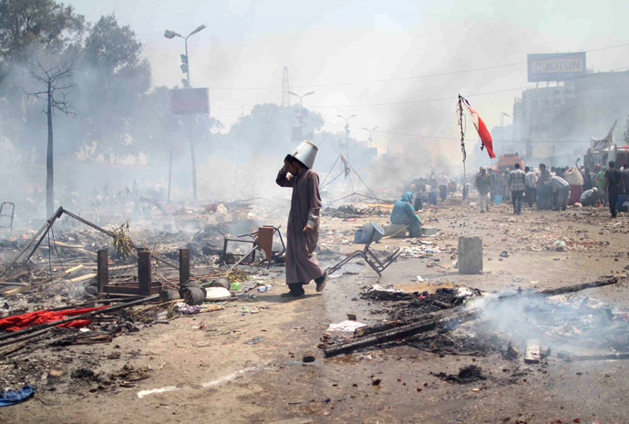 A supporter of Egypt's ousted president Mohamed Morsi walks through the debris following clashes with police in Cairo on August 14, 2013, as security forces backed by bulldozers moved in on two huge pro-Morsi protest camps, launching a long-threatened crackdown that left dozens dead. (AFP Photo)