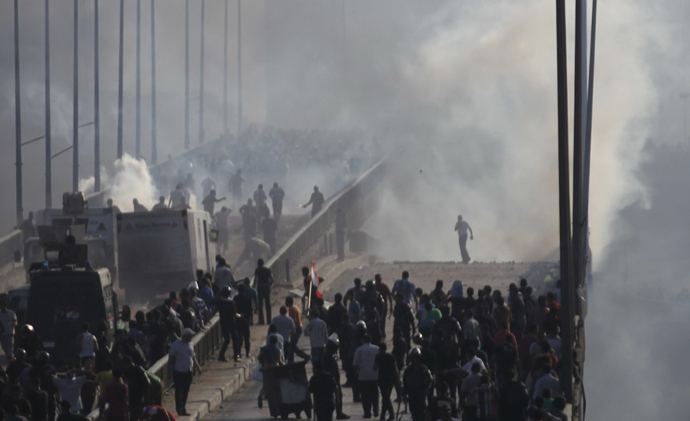 Members of the Muslim Brotherhood and supporters of ousted Egyptian President Mohamed Mursi flee from tear gas and rubber bullets fired by riot police during clashes, on a bridge leading to Rabba el Adwia Square where they are camping, in Cairo August 14, 2013 (Reuters / Amr Abdallah Dalsh)