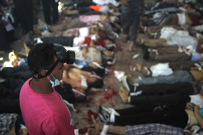 A man looks at bodies laid out in a make shift morgue after Egyptian security forces stormed two huge protest camps at the Rabaa al-Adawiya and Al-Nahda squares where supporters of ousted president Mohamed Morsi were camped, in Cairo, on August 14, 2013 (AFP Photo / Mosaab El-Shamy)