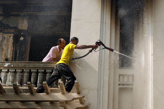 People try to put out a fire in a government building after it was set ablaze in Giza's district of Cairo, August 15, 2013 (Reuters / Muhammad Hamed)