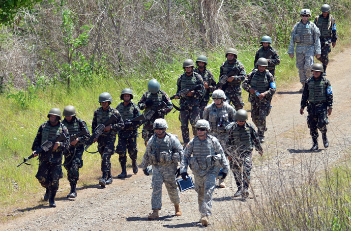 Philippine (L) and US (R) troops walk to their base after conducting a squad live fire exercise as part of the annual joint Philippine-US military exercise at Fort Magsaysay in Nueva Ecija province, north of Manila on April 11, 2013. (AFP Photo/Ted Aljibe)