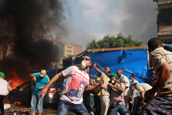 Supporters of the Muslim Brotherhood and Egypt's ousted president Mohamed Morsi throw stones during clashes with security forces in Cairo on August 14, 2013, as security forces backed by bulldozers moved in on two huge pro-Morsi protest camps, launching a long-threatened crackdown that left dozens dead. (AFP Photo)