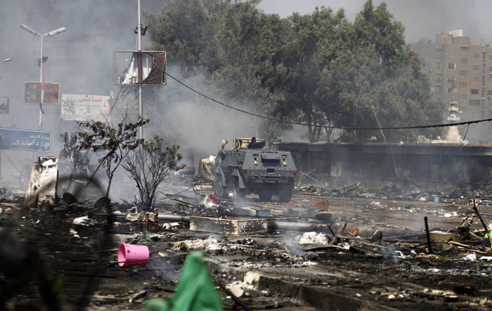 An Egyptian security forces' armoured vehicle drives amidst the remains of a protest camp set up by supporters of ousted president Mohamed Morsi and members of the Muslim Brotherhood after a crackdown on August 14, 2013 near Cairo's Rabaa al-Adawiya mosque. (AFP Photo)