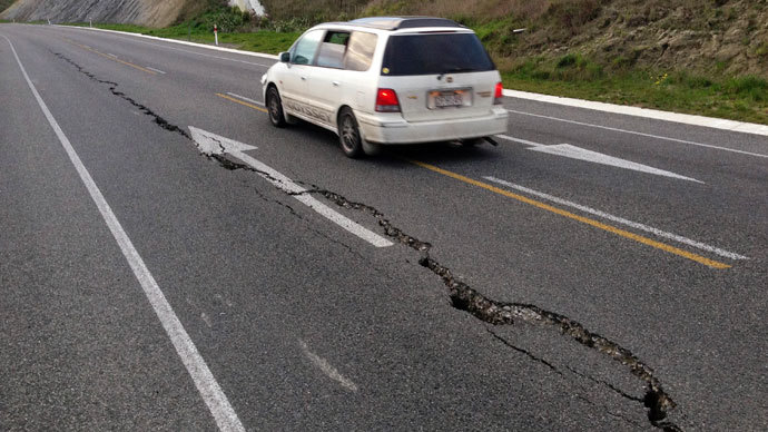 A car drives past a crack in a road after an earthquake on the outskirts of the town of Seddon in the Marlborough region, on New Zealand's South Island August 16, 2013.(Reuters / Anthony Phelps)