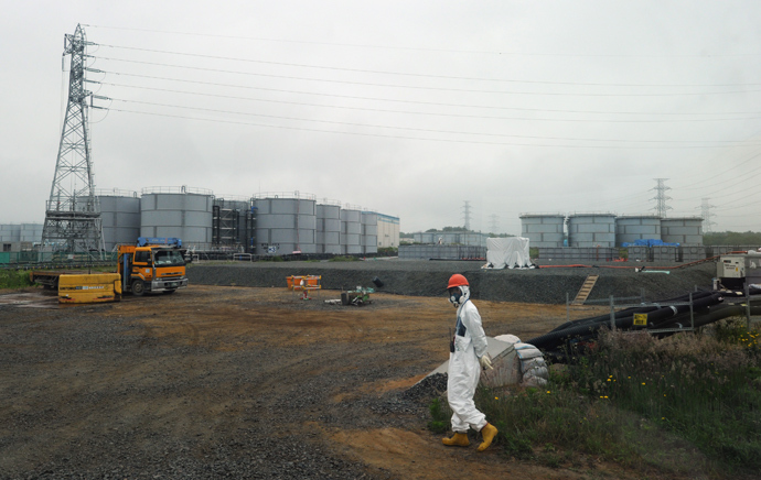 A construction worker walks near water tanks at Japan's Fukushima Dai-ichi nuclear plant in Okuma town in Fukushima prefecture (AFP Photo)