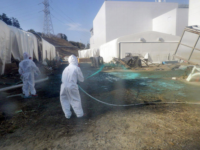 Workers spraying resin on the ground near the reactor buildings to protect the spread of radioactive substances at TEPCO's Fukushima Daiichi nuclear power plant at Okuma town in Fukushima prefecture (AFP Photo)