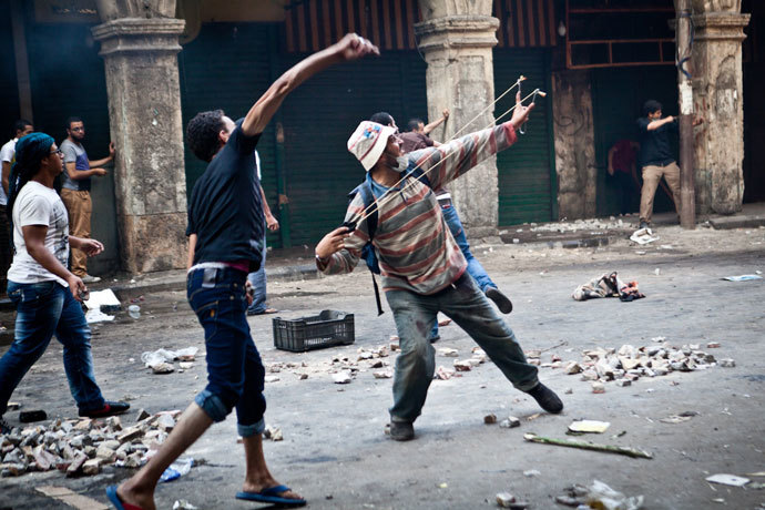 Supporters of ousted president Mohamed Morsi throw stones as they clash with security officers in Cairo's Ramses Square, on August 16, 2013.(AFP Photo / Virgnie Nguyen Hoang)