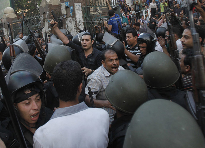 A plain clothes policeman (upper left) points his gun as security forces escort Muslim Brotherhood members through supporters of the interim government installed by the army from the al-Fath mosque on Ramses Square in Cairo August 17, 2013. (Reuters/Amr Abdallah Dalsh)